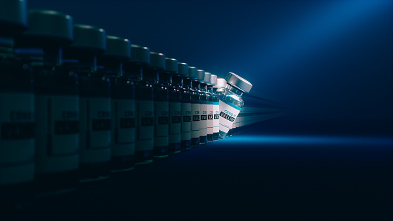 Covid-19 vaccine vials in a row on blue background. One vial standing out from others under spotlight.
